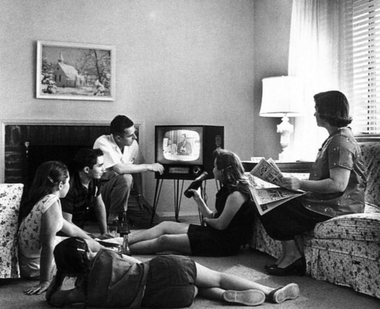 Foto em preto e branco de uma família vendo televisão em 1958.