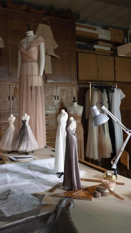 Imagem de um estúdio com manequins em tamanho real e miniatura vestidos como deusas gregas.