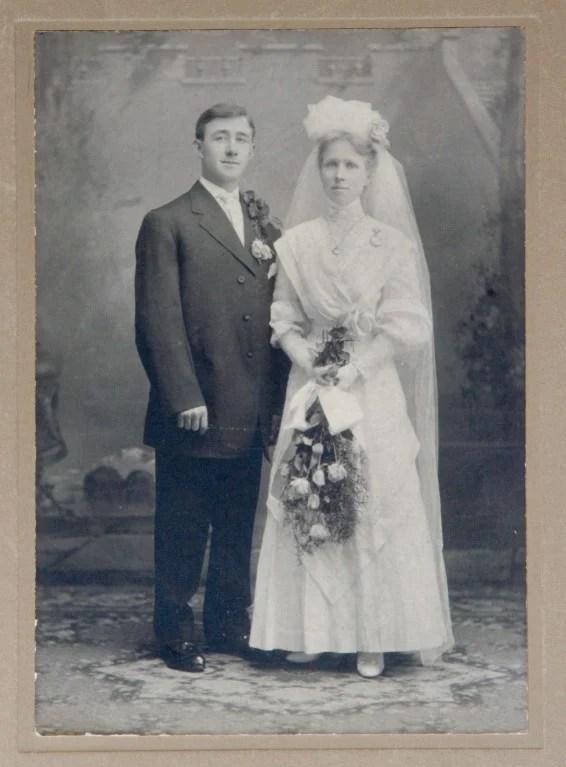 Mulher posando ao lado do seu marido por volta de 1900.