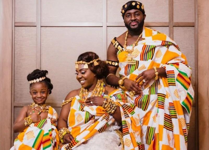 Foto de um casal e uma menina vestidos com roupa de cerimônia de casamento típica do Gana.