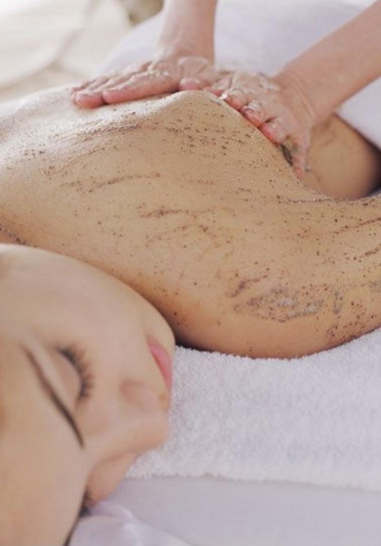 Foto de mulher fazendo esfoliação no corpo