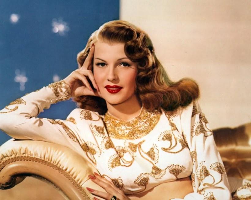 A atriz Rita Hayworth posando em um sofá
