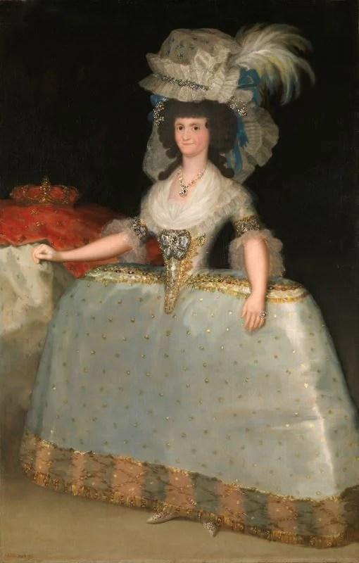 Mulher posando com um vestido e chapéu muito volumosos