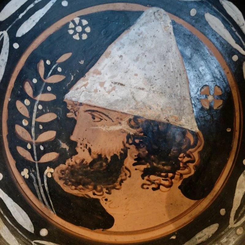 Ilustração de um homem com um chapéu píleo com forma cônica