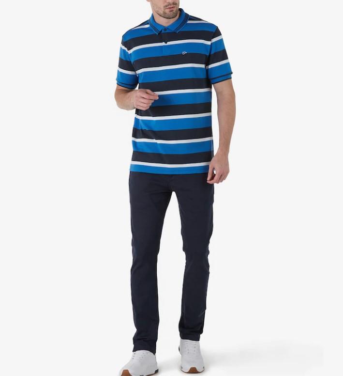 Homem de blusa polo listrada azul, jeans, e tênis branco