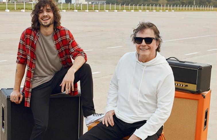 Fiuk e Fábio Júnior sentados lado a lado e rindo.
