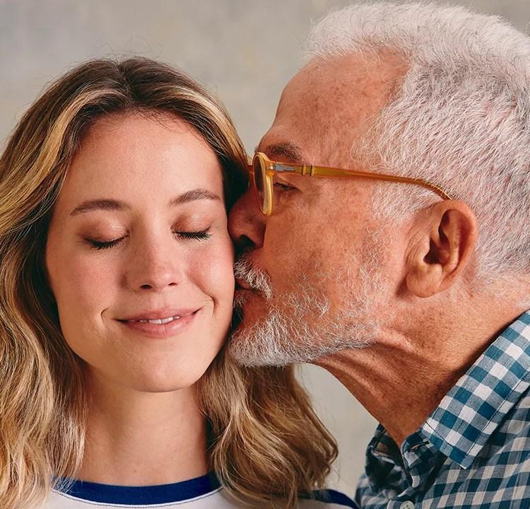 Um pai mais velho dá um beijo na bochecha da filha loira.