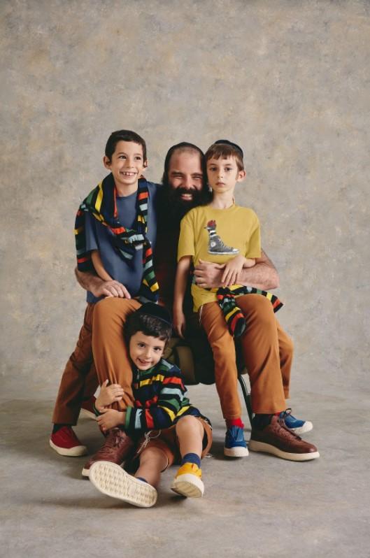 Um pai e seus três filhos judeus usando roupas coloridas