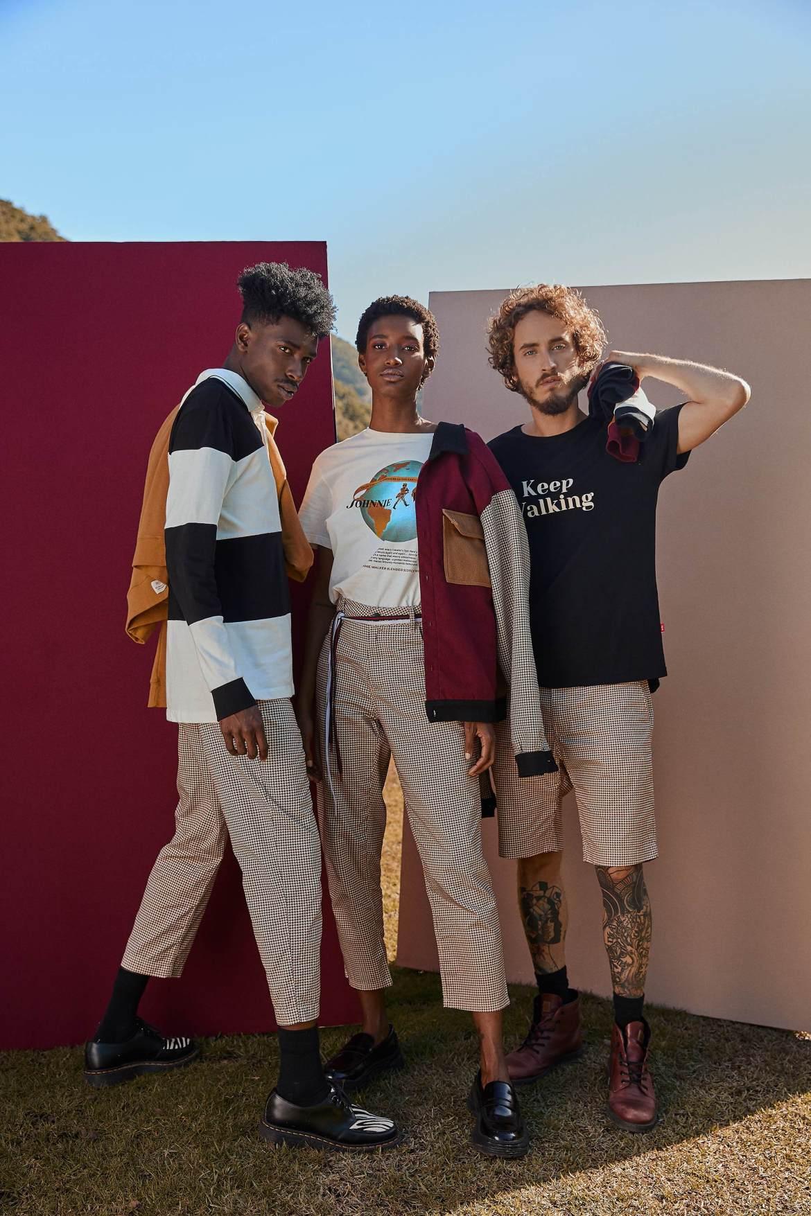 Três modelos em pé juntos, usando roupas de cores mostarda, vinho, branco e azul marinho