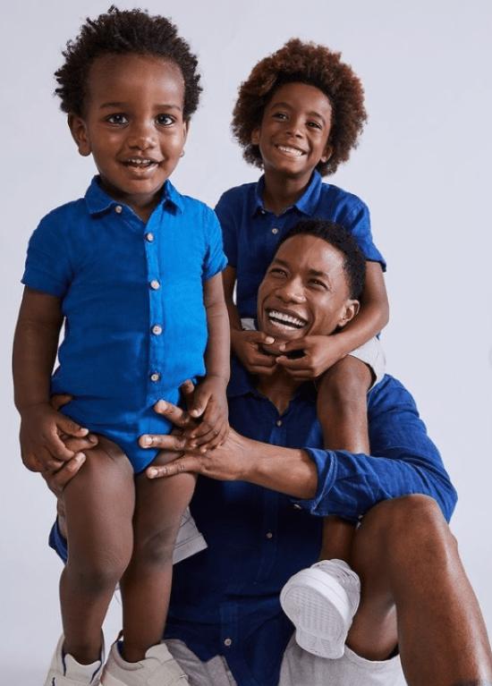 Pai e dois filhos com roupas de linho azul