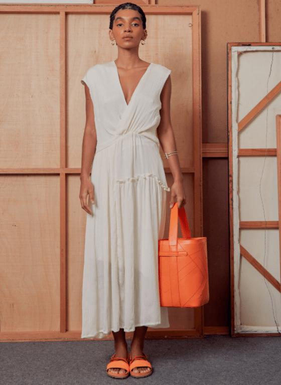 Modelo usa vestido branco e segura bolsa laranja
