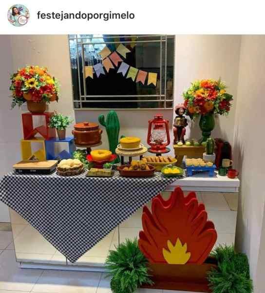 Foto de aparador transformado em mesa de festa junina com comidinhas e decoração de bandeirolas