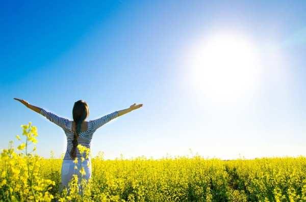 Foto de mulher em campo de flores amarelas com braços abertos para o sol