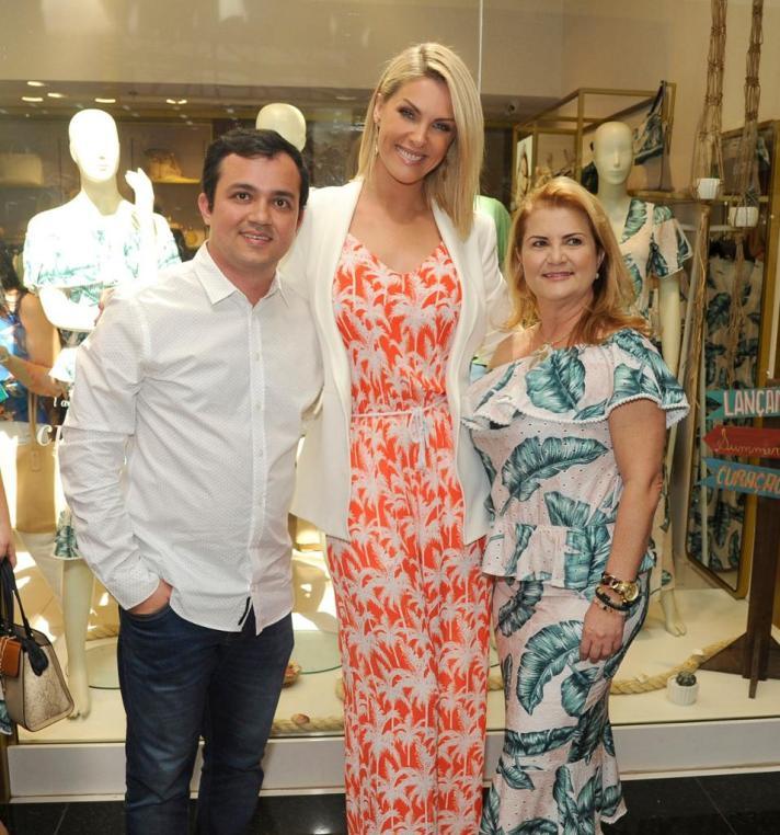 Ana Hickmann com dois integrantes da sua loja de roupas.