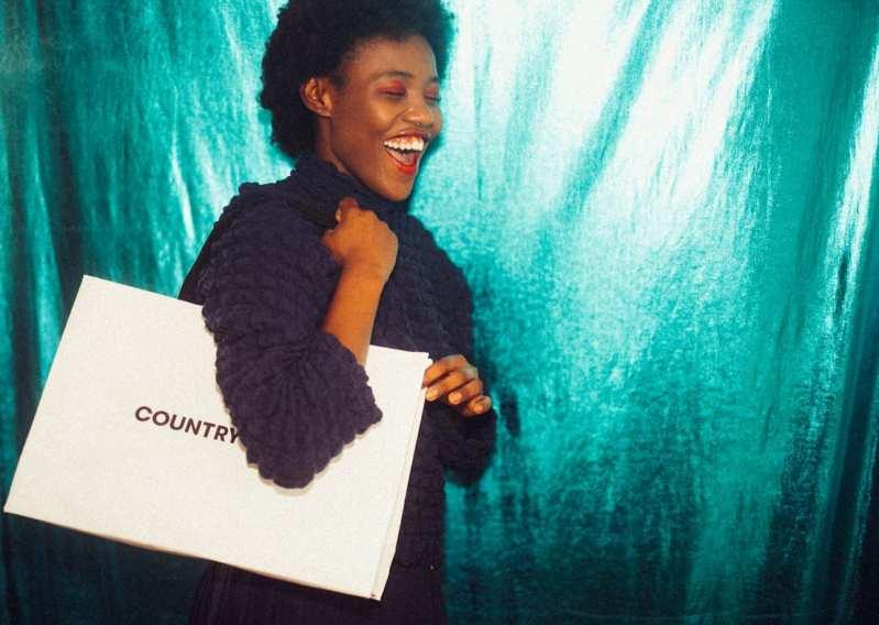 Mulher negra com sorrisão e sacola de compras