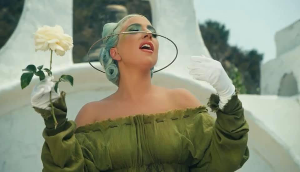 Lady gaga em 911 com vestido verde, aurela segurando uma rosa branca