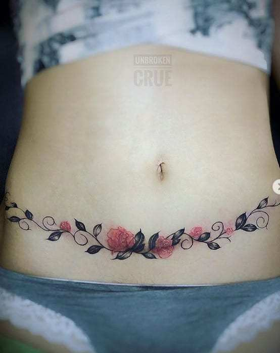 Tatuagem delicada de ramo de flores cobre cicatriz barriga