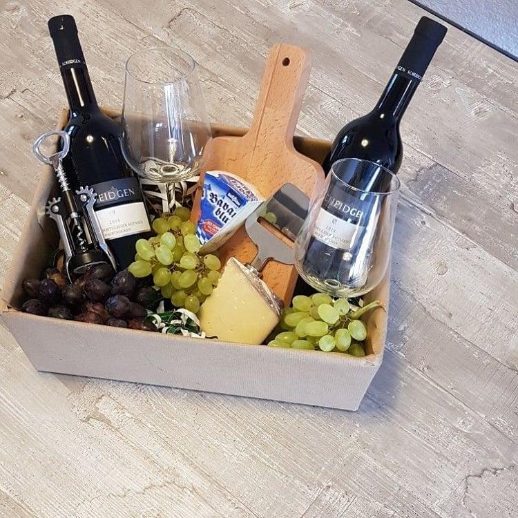foto de caixa com vinhos, taças, uvas e queijos