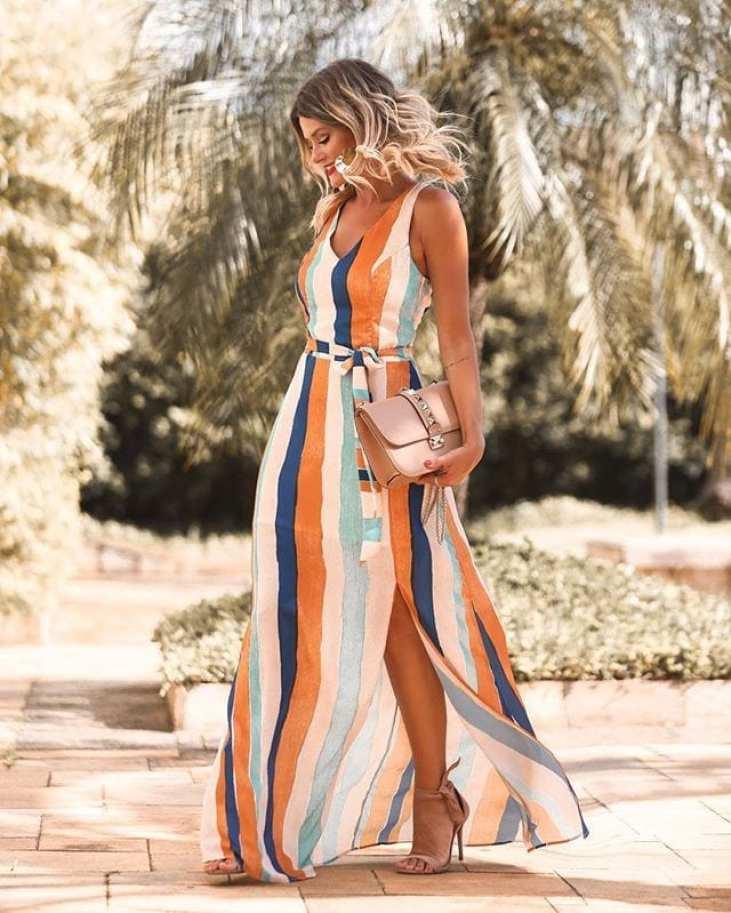 Mariana Dalla vestindo vestido comprido aberto nas pernas de listras.