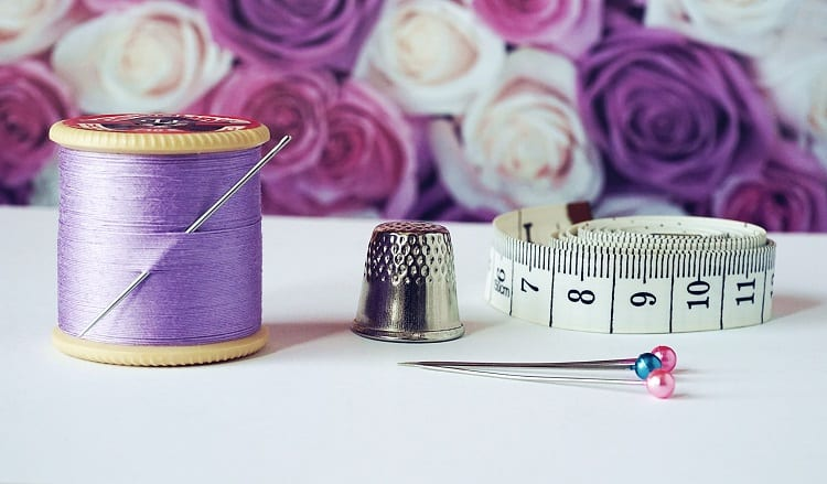 linha, agulha, dedal e fita métrica sobre uma bancada