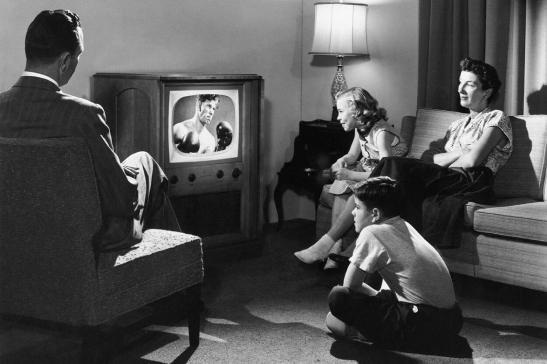 Foto antiga de família assistindo televisão.