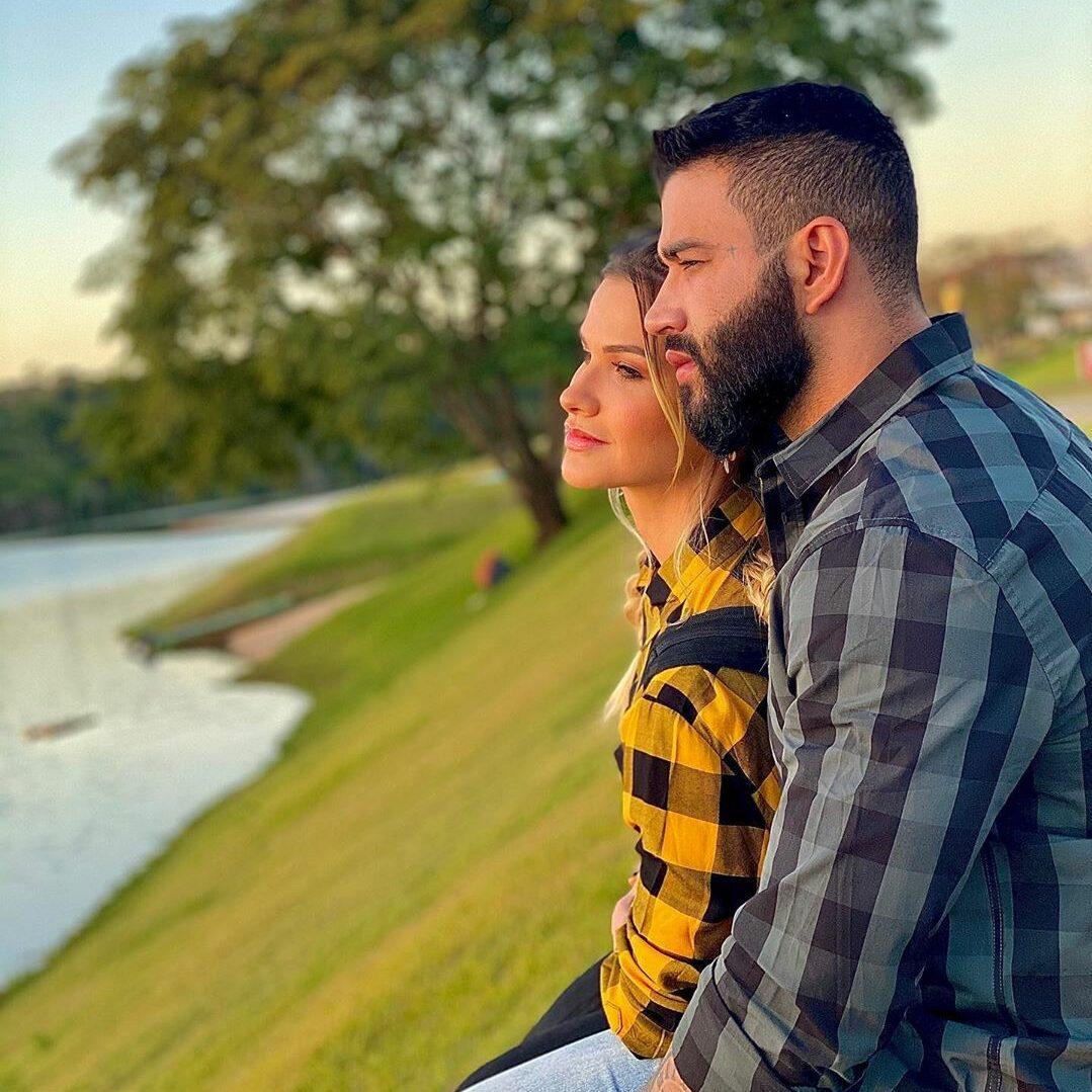 Foto de Andressa e Gusttavo olhando para lago.