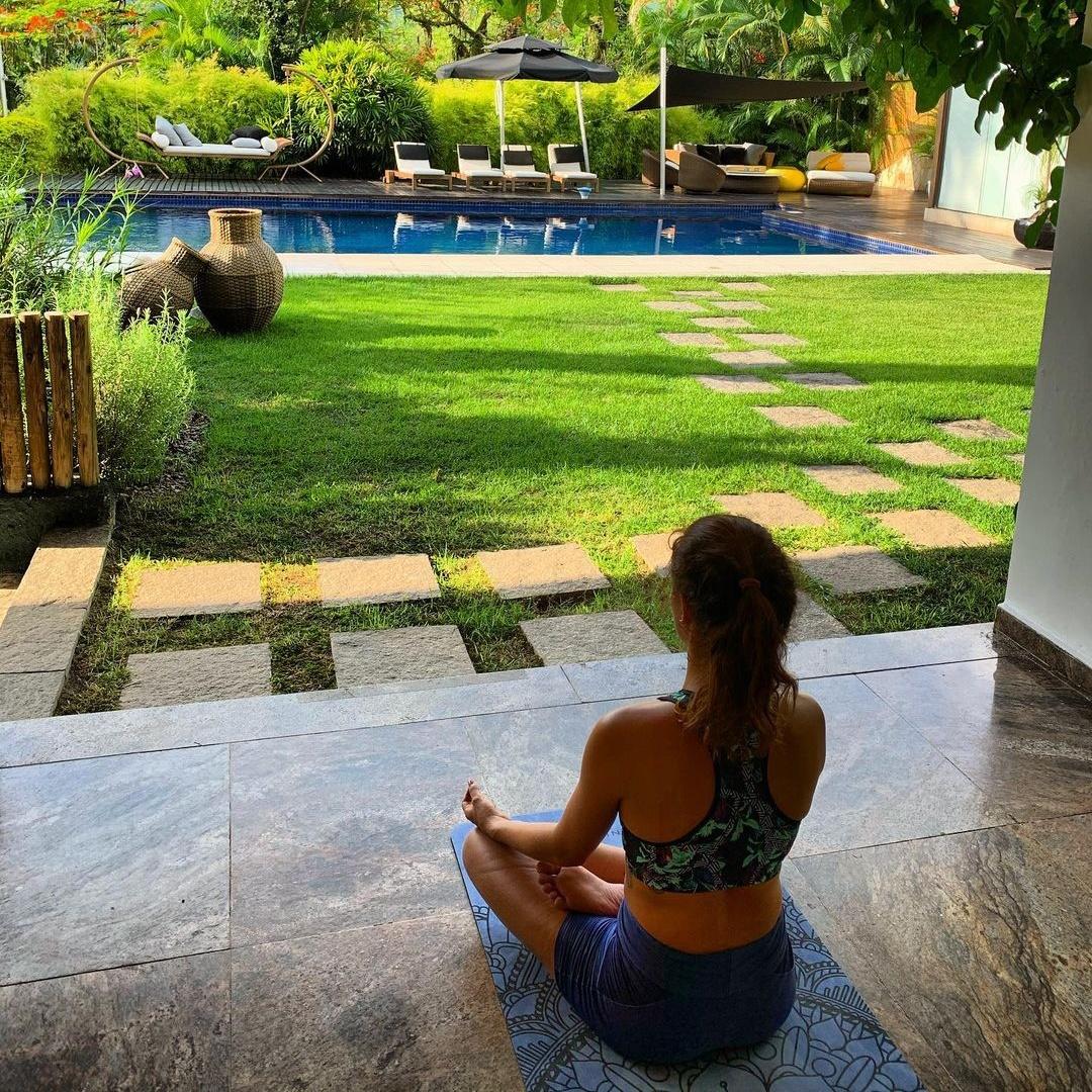 Isis medita de frente para piscina.