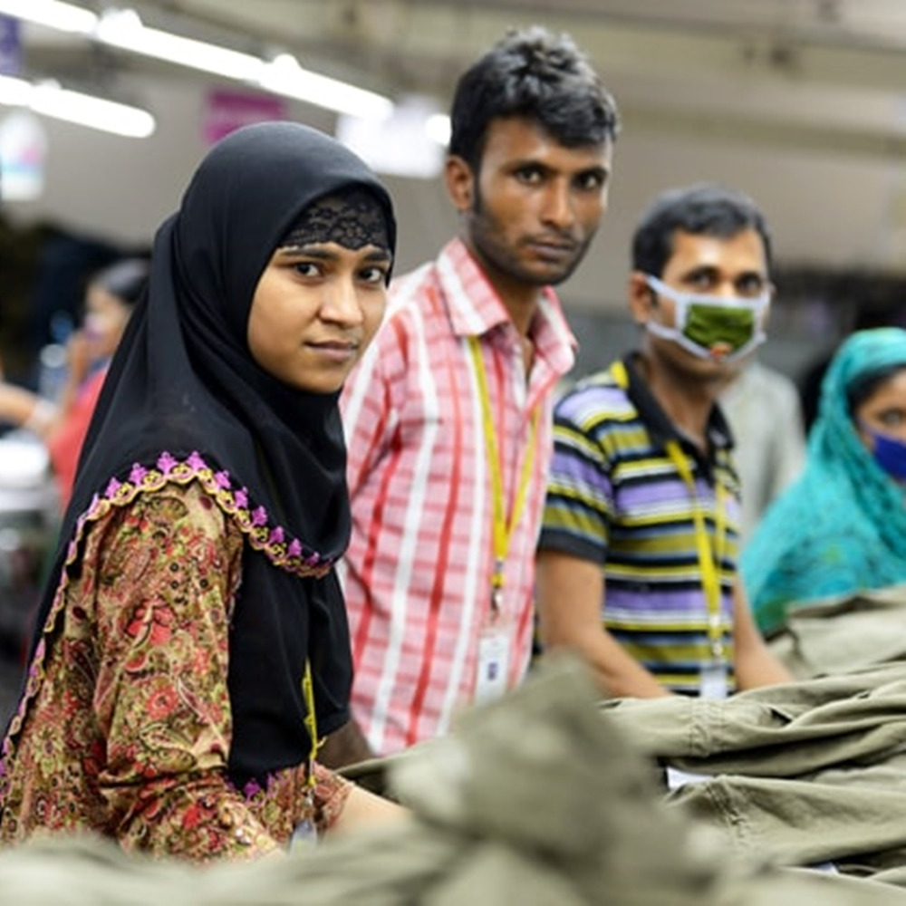 Homens e mulheres em trabalhado de roupas para a moda.