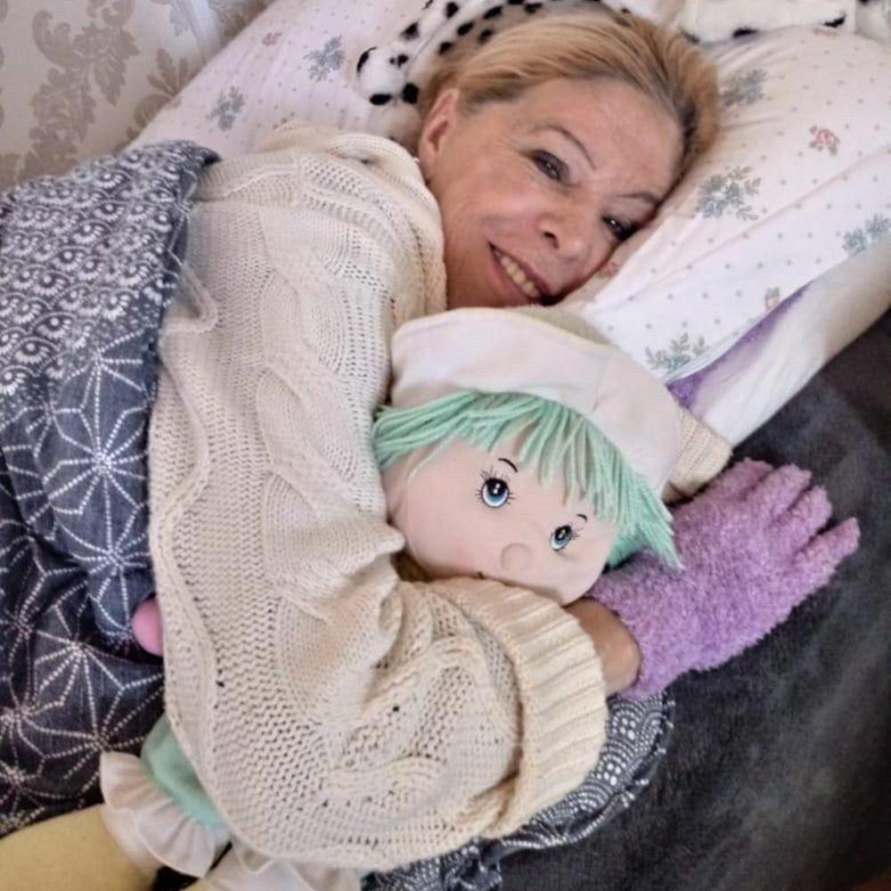 Vanusa sorridente se recuperando em cama de hospital.