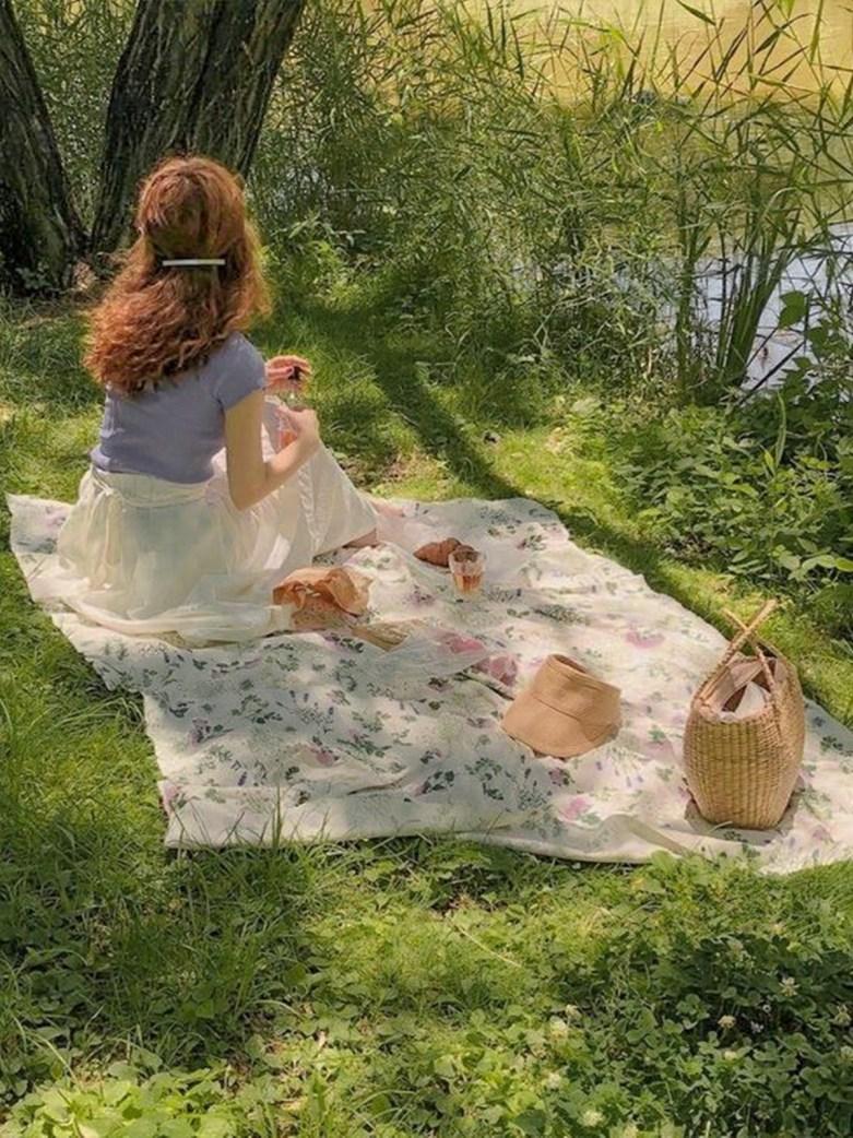 Cottagecore: Jovem fazendo piquenique em campo.