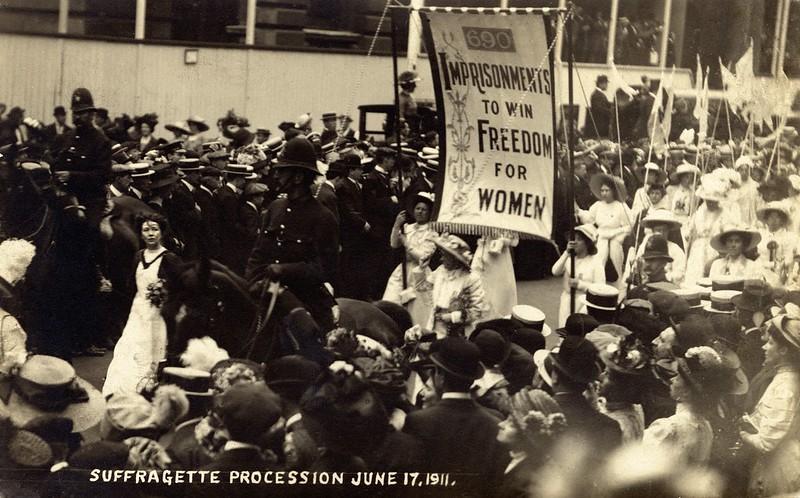 Procissão com Christabel Pankhurs, em 1911, com uma faixa onde se lê: Prisões para ganhar a liberdade para as mulheres.