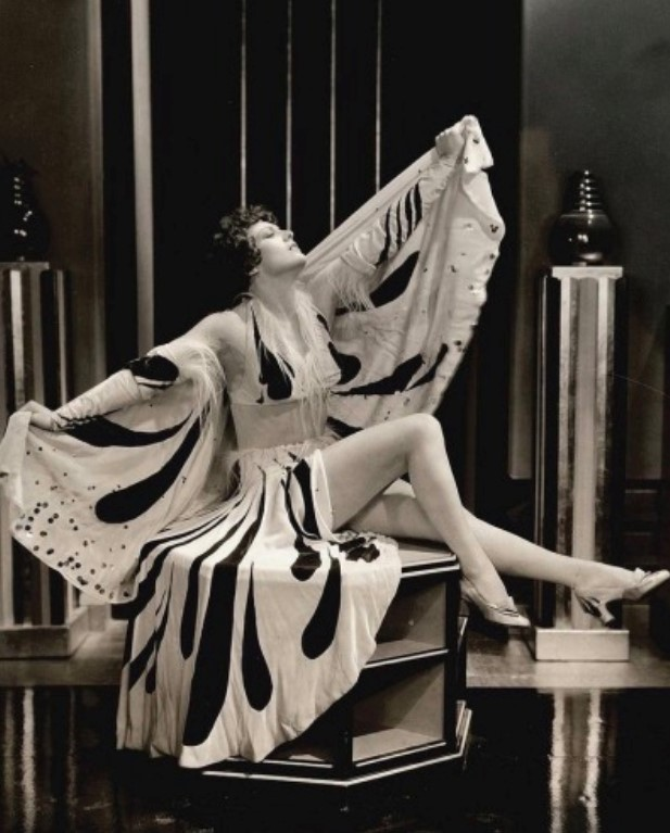 Foto da atriz Joan Crawford posando com um vestido decotado e longo, em 1932.