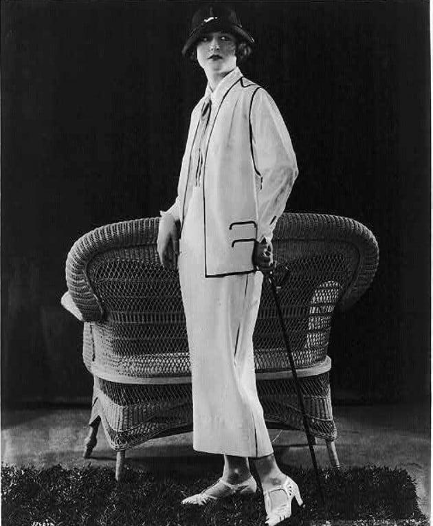 Mulher posando com um modelo de roupa branco e chapéu, em 1924. Look da Moda e Cidadania nos anos 20 e 30.