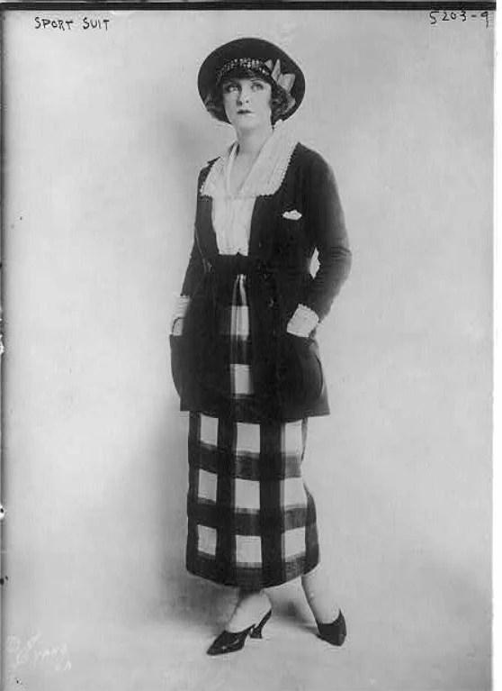 Mulher posando com um modelo de roupa dos anos 1920, com uma saia longa xadrez e chapéu. Look da Moda e Cidadania nos anos 20 e 30.