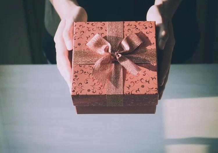 mãos segurando uma caixinha de presente