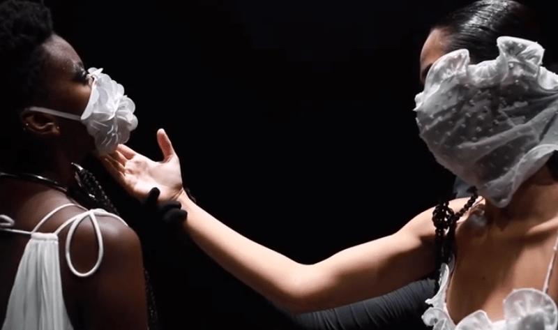 SPFW: Duas modelos se olhando. A da esquerda usa máscara branca com bordado e da direita usa máscara transparente com flocado.