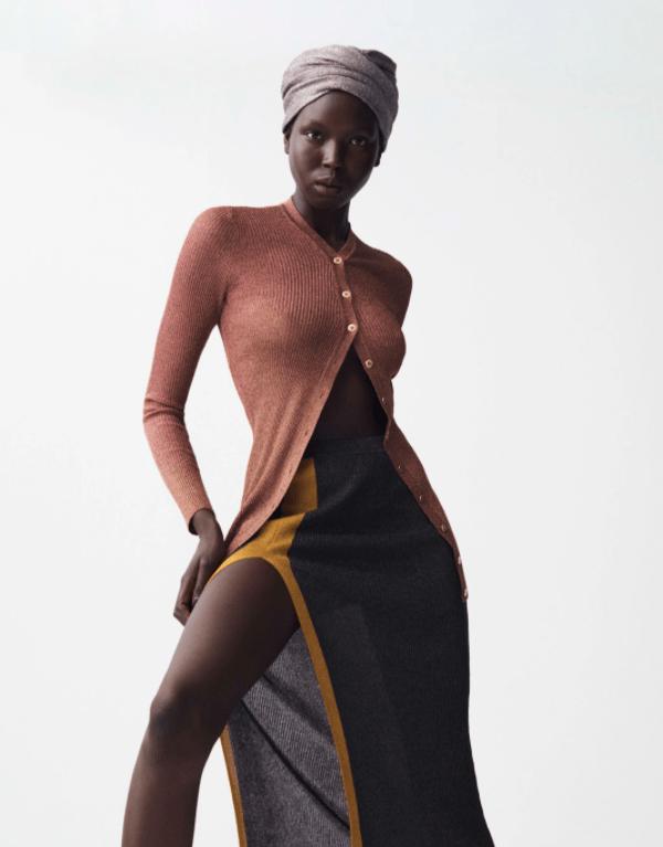 Modelo usa blusa de tricô com abotoamento e saia com fenda lateral