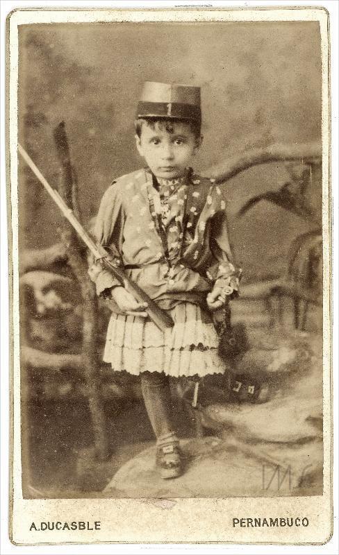 Retrato de uma criança em Pernambuco por volta de 1885 vestindo uma espécie de vestido e chapéu.