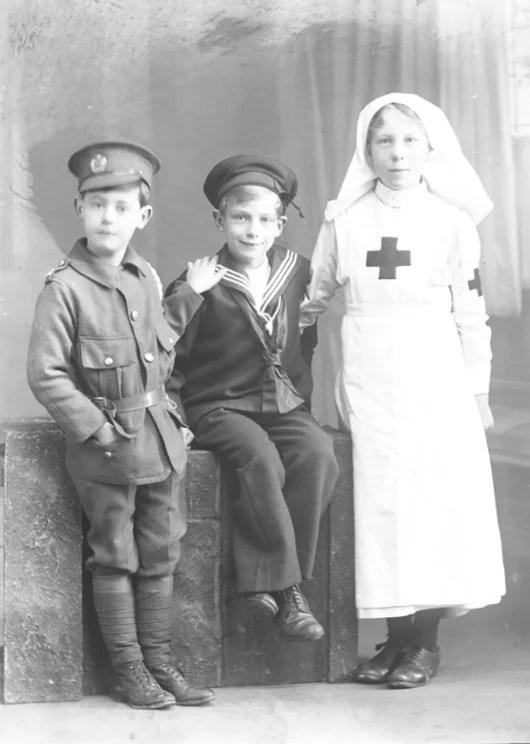 Crianças da família Dickinson vestidas com uniformes do exército, marinha e enfermeira da Primeira Guerra Mundial.