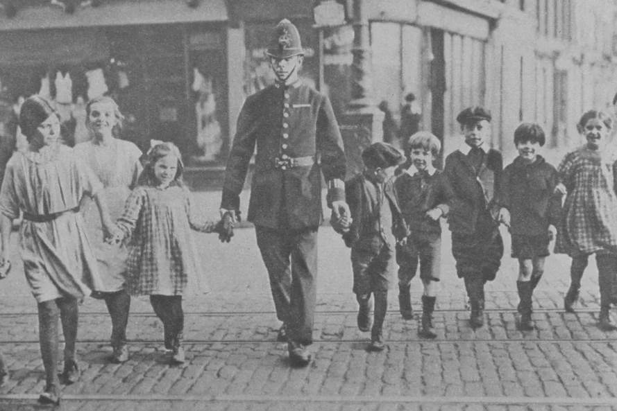 Grupo de crianças em Londres sendo guiadas por um policial, em 1920.