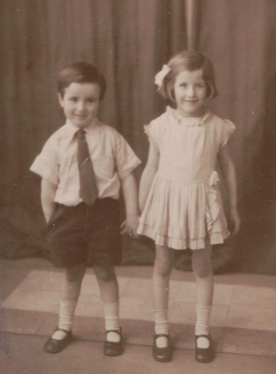 Um casal de irmãos vestido com um exemplo da moda infantil no início do século XX.
