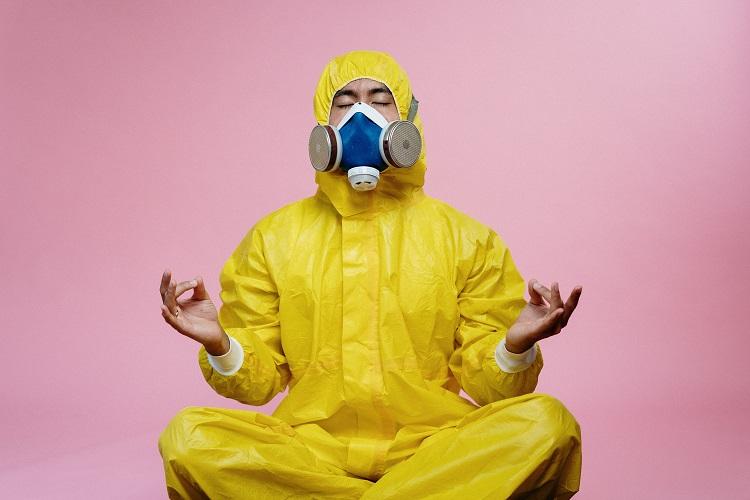 homem fazendo meditação com roupa protetora contra COVID-19