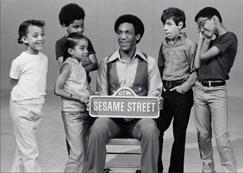 Fotos dos anos 70 de um grupo de crianças ao redor de Bill Cosby a segurar uma placa da Vila Sésamo.