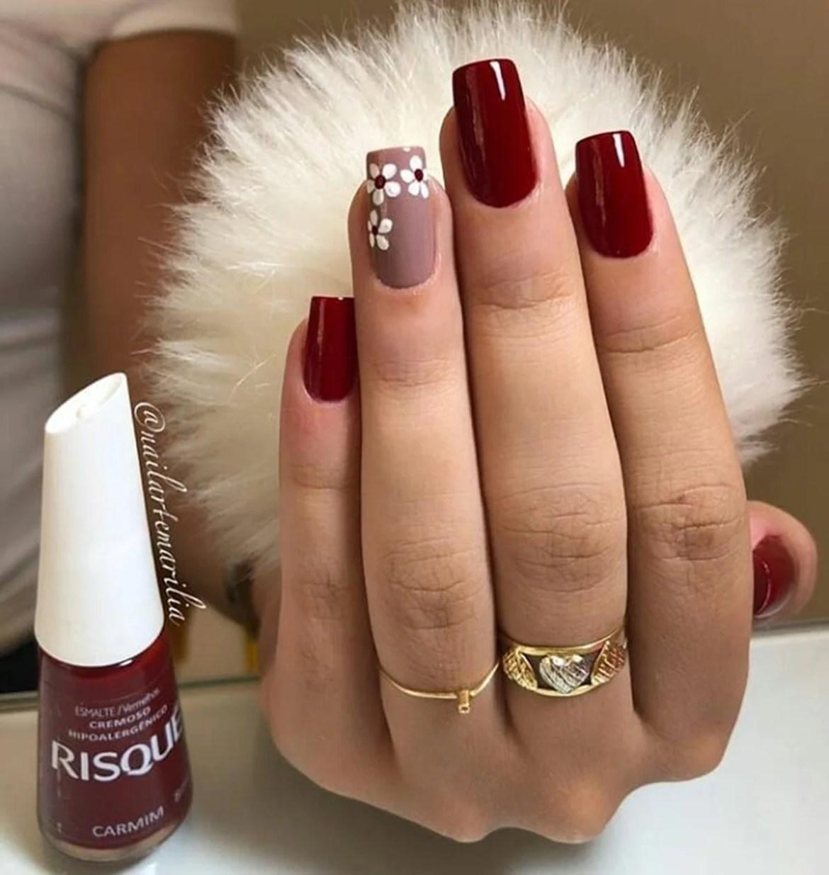 Simples vermelho escuro com flores no dedo anelar em nude.