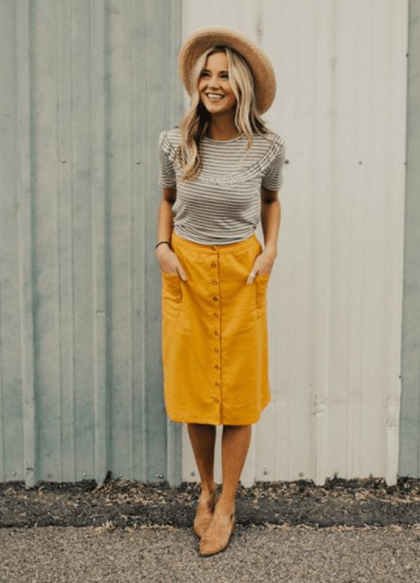 Mulher usa blusa listrada cinza e saia amarela