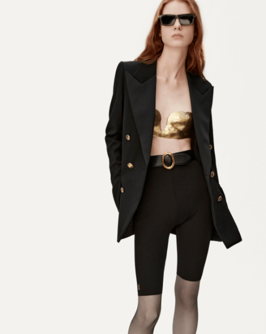 Blazer, bermuda ciclista, meia-calça, cinto e top dourado.