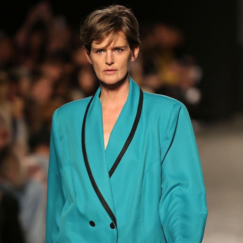 Artista usa terno azul em desfile.