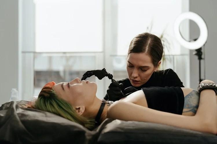 mulher deitada em maca sendo tatuada