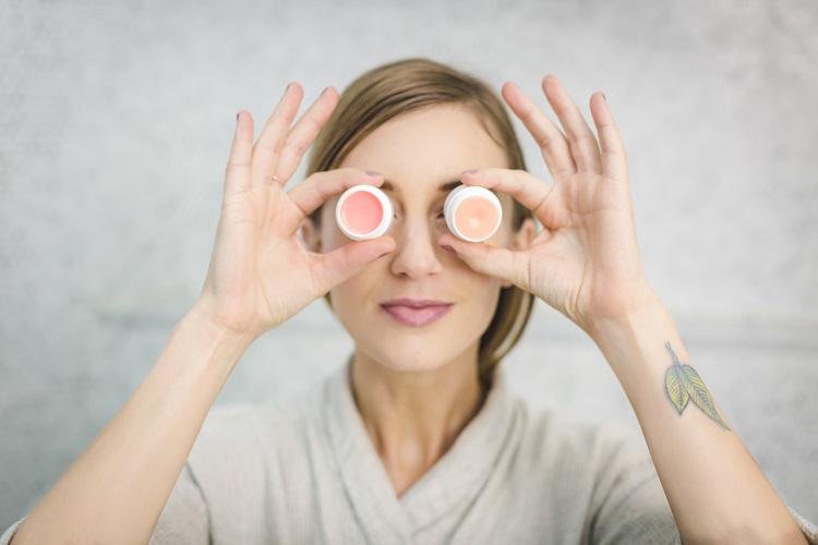 mulher segurando dois potes de creme de clareamento sobre os olhos