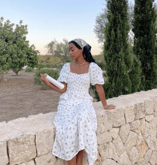 Vestido Cottagecore, modelo sentada em muro lendo